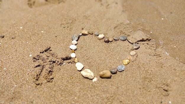 砂の上に石を描くハートのシンボル。夏休み