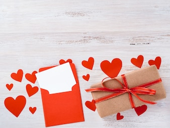 Symbol of Valentine's day - gift box in kraft brown paper with red ribbon, envelope