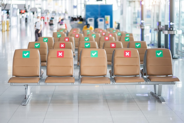 Symbol sticker on chair in international airport. new normal and social distancing concepts, protection coronavirus disease (covid-19) infection