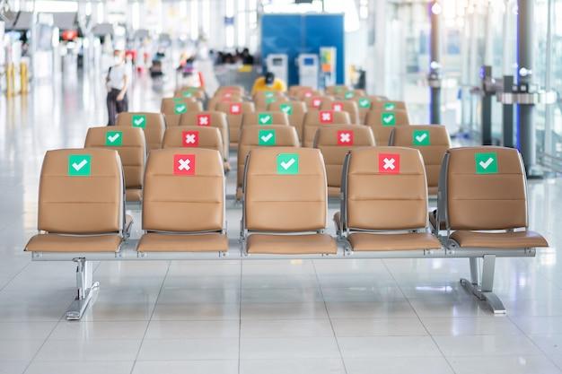 Наклейка с символом на стуле в международном аэропорту. новые концепции нормального и социального дистанцирования, защита от инфекции, вызванной коронавирусом (covid-19)