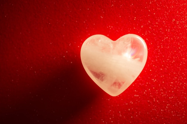 Symbolic photo of transparent stone in shape of a heart on red background