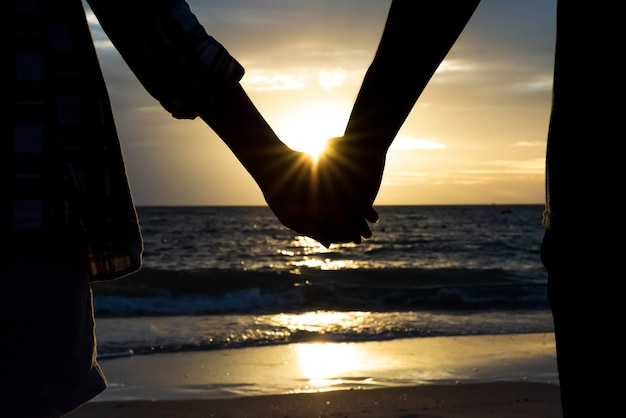 Symbols of love. silhouette couple of man and woman hand holding together.