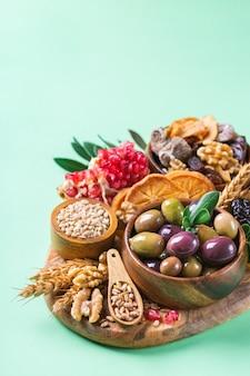 Символы иудейского праздника ту бишват, новый год рош ха-шана из елок. смесь сухофруктов, фиников, инжира, винограда, ячменя, пшеницы, оливок, граната на зеленом столе. скопируйте космический фон