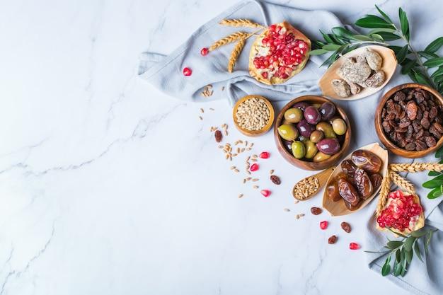 유대교 휴일 tu bishvat, 나무의 rosh hashana 새해의 상징. 대리석 테이블에 말린 과일, 대추, 무화과, 포도, 보리, 밀, 올리브, 석류를 섞으세요. 공간 배경 복사