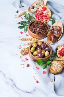 Символы иудейского праздника ту бишват, новый год рош ха-шана из елок. смесь сухофруктов, фиников, инжира, винограда, ячменя, пшеницы, оливок, граната на мраморном столе. скопируйте космический фон