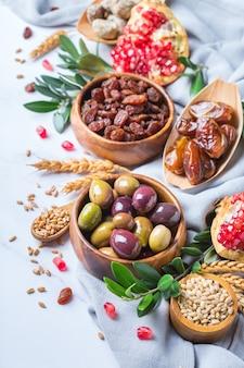 Символы иудейского праздника ту бишват, новый год рош ха-шана из елок. смесь сухофруктов, фиников, инжира, винограда, ячменя, пшеницы, оливок, граната на мраморном столе.