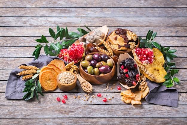 Символы иудейского праздника ту бишват, новый год рош ха-шана из елок. смесь сухофруктов, фиников, инжира, винограда, ячменя, пшеницы, оливок, граната на деревянном столе. скопируйте космический фон