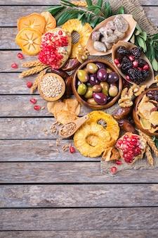 Символы иудейского праздника ту бишват, новый год рош ха-шана из елок. смесь сухофруктов, фиников, инжира, винограда, ячменя, пшеницы, оливок, граната на деревянном столе. скопируйте космический плоский фон