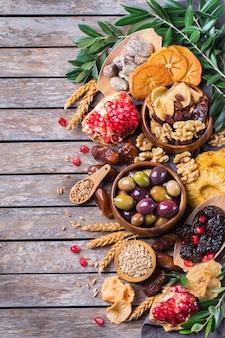 Символы иудейского праздника ту бишват, новый год рош ха-шана из елок. смесь сухофруктов, фиников, инжира, винограда, ячменя, пшеницы, оливок, граната на деревянном столе. плоский фон