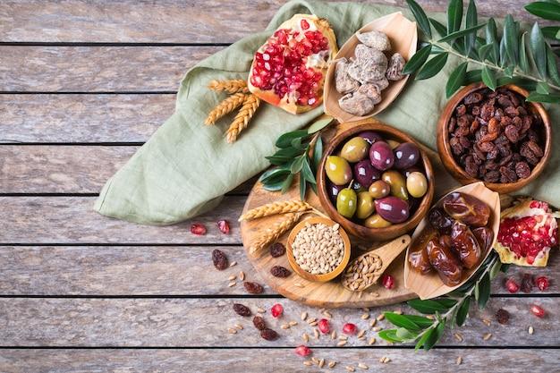 Символы иудейского праздника ту бишват, новый год рош ха-шана из елок. смесь сухофруктов, фиников, инжира, винограда, ячменя, пшеницы, оливок, граната на деревянном столе. вид сверху, плоский фон