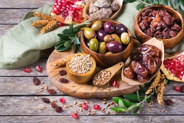 Символы иудейского праздника ту бишват, новый год рош ха-шана из елок. смесь сухофруктов, фиников, инжира, винограда, ячменя, пшеницы, оливок, граната на деревянном столе.