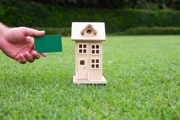 신용 및 계약을 돌보는 부동산 투자자의 상징. 손에 장난감 집과 신용 카드입니다.