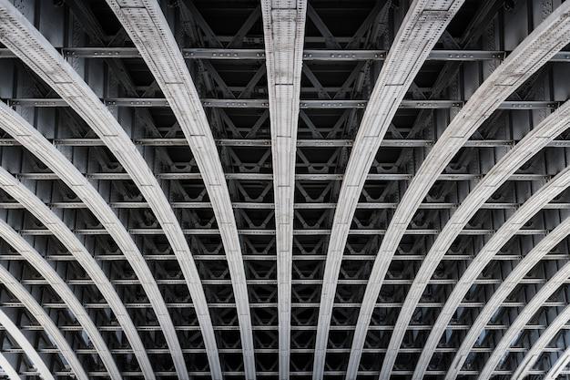 ロンドンのテムズ川に架かる橋の下の対称的な鉄骨フレーム。