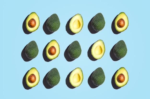 Симметричная композиция из ломтиков авокадо на синем фоне. вид сверху. Premium Фотографии
