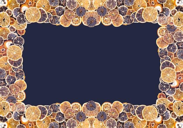 Symmetrical frame of dry slices of orange and grapefruit. fruit chips background. decorative banner.