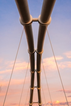 Symmetrical steel pipes supporting a suspension bridge over a river.