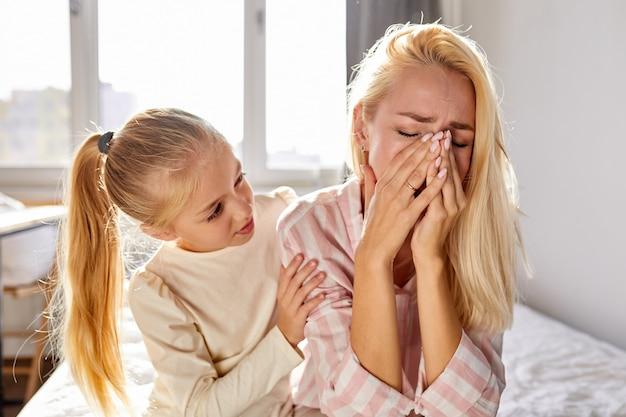 Сочувственная девочка успокаивает свою плачущую мать