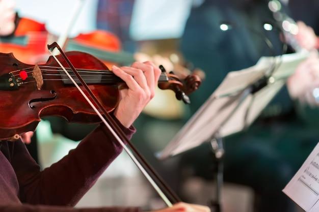Симфоническая музыка. музыкант играет на скрипке в оркестре. сосредоточьтесь на луке.