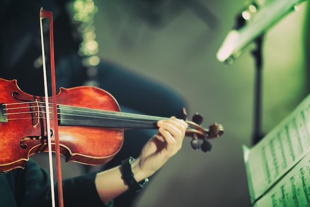 Симфоническая музыка. женщина играет на скрипке в оркестре. винтажная тонировка.