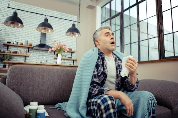 風邪の症状。くしゃみをする準備ができている間、ティッシュペーパーを持っている暗い病気の人