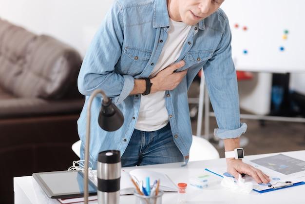 心臓発作の症状。職場の後ろに立って、左手をテーブルに置き、心に触れている不活性な男