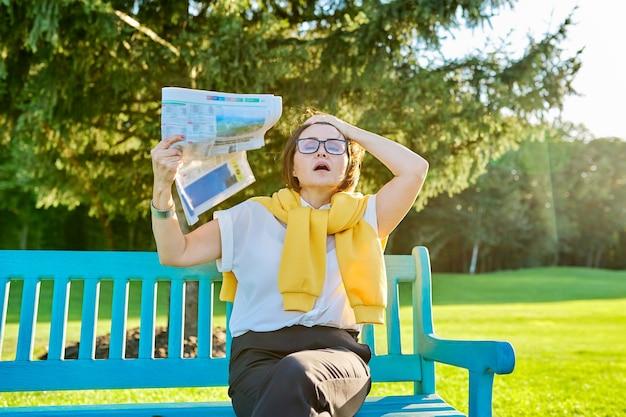 成熟した女性の更年期障害の症状、女性が冷やすために新聞を振る、暑く感じる、年齢ホルモンの変化。公園のベンチに女性