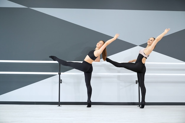 体操を練習している同期された女性インストラクターと女の子