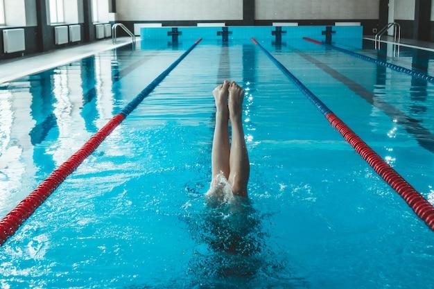 Спортсмены по синхронному плаванию тренируются в одиночестве в бассейне