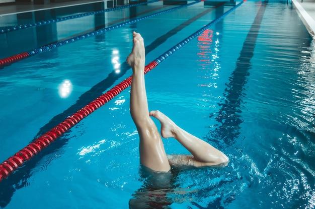 シンクロナイズドスイミングのアスリートがプールで一人でトレーニング