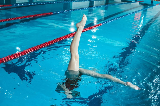 Synchronized swimming athlete trains alone in the swimming pool