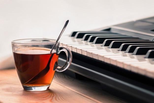 Синтезатор и чашка чая на деревянном столе