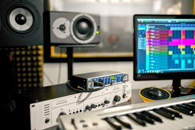Синтезатор крупным планом, оборудование студии звукозаписи на фоне. аудио колонки, микшер и монитор, рабочее место звукорежиссера