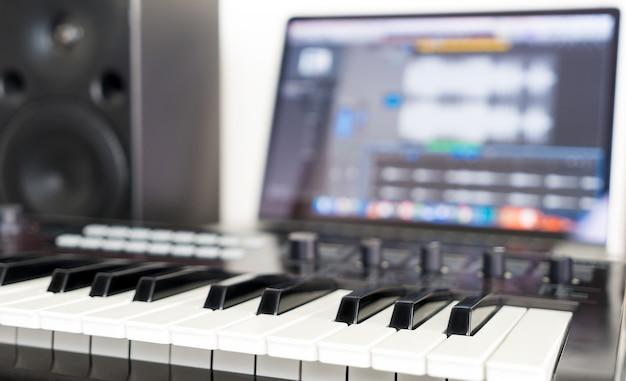 Synthesizer keyboard lying on music studio working desktop