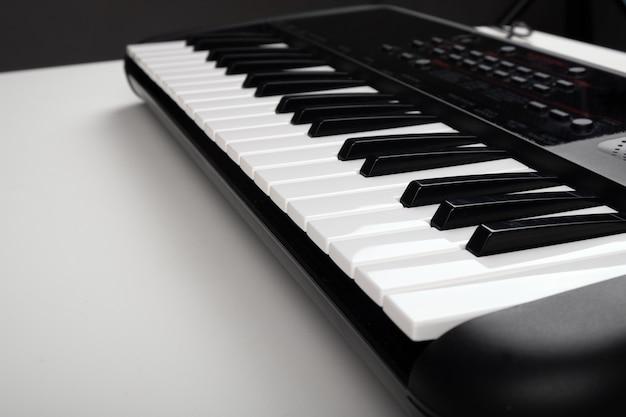 Синтезатор на белом столе, крупный план музыкального инструмента.