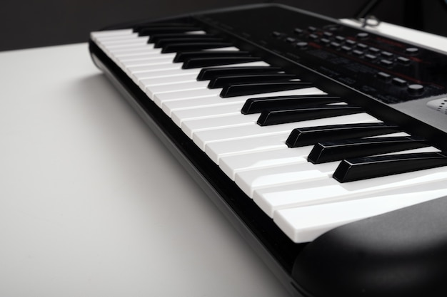 Synthesizer on a white table,musical instrument closeup.