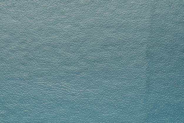 Синтетическая кожа синего цвета для фона. макрофотография крупным планом, вид декоративного материала текстуры, дизайн фона рисунка для плаката, брошюры, обложки книги и каталога.