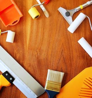 Синтетические кисти, поролоновые валики, съемник, шпатели и другие инструменты для домашнего ремонта на деревянном фоне.