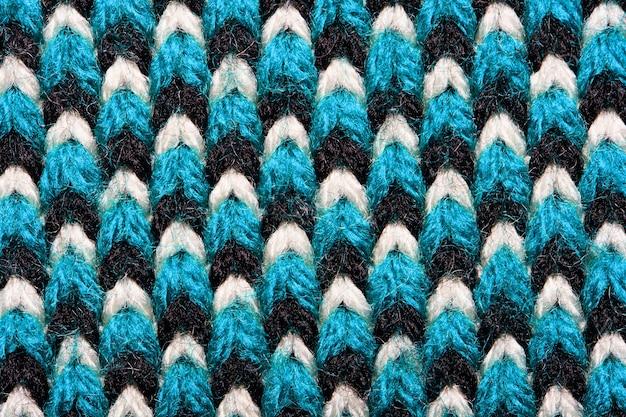 Синтетическое трикотажное полотно с элементами узора из голубой, черной и белой пряжи крупным планом. задний план