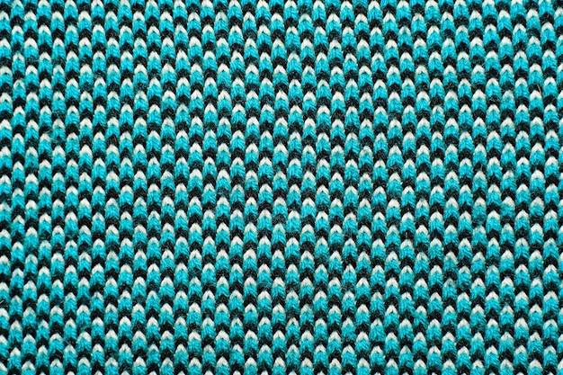 파란색, 검은 색 및 흰색 원사의 패턴 요소와 합성 니트 직물을 닫습니다. 니트웨어