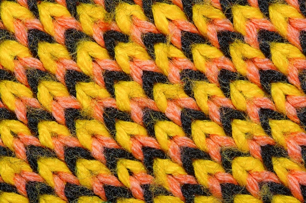 Synthetic knitted fabric with pattern elements of yellow, black and red yarns close up. multicolor patterned knitted fabric texture. background