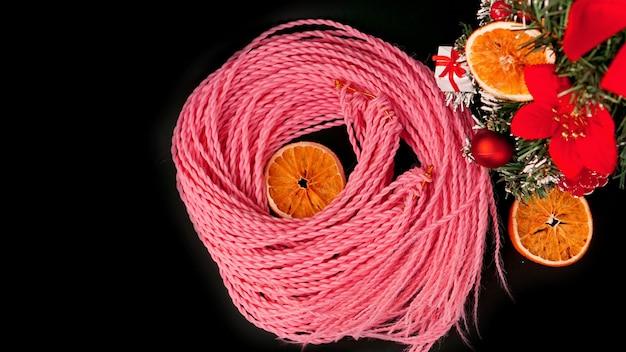 Синтетические розовые косы канекалон - новогоднее фото с украшением на черном. новогоднее фото для магазина или парикмахерских, парикмахерских