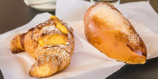 イタリア、シチリア島のシラキュース。バーテーブルで朝食として提供されるクリーム入りの伝統的な新鮮なブリオッシュ。自然光、スタジオなし。