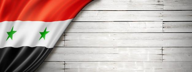 Флаг сирии на старой белой стене. горизонтальный панорамный баннер.