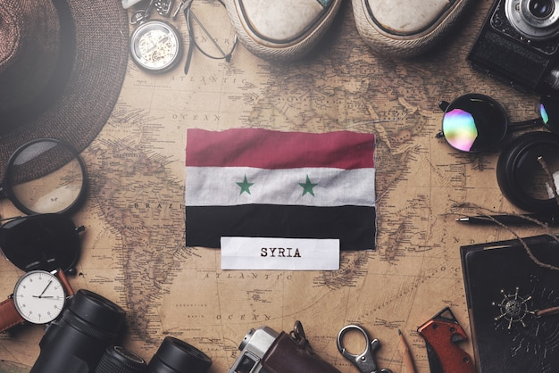 Syria flag between traveler's accessories on old vintage map. overhead shot