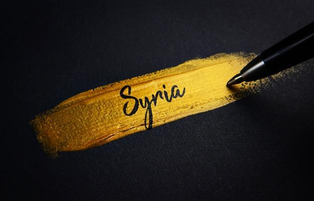 Syria handwriting text on golden paint brush stroke