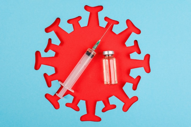 Syringe and ampoule with vaccine and red abstract virus,