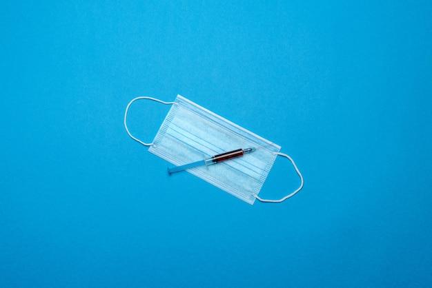 青のcovid-19ウイルスを防ぐための注射器と使い捨てフェイスマスク