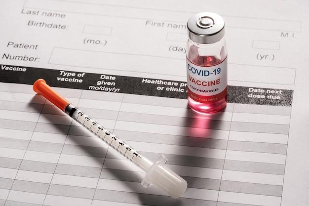Covid-19に対するワクチン接種用の注射器とガラスのワクチンバイアル
