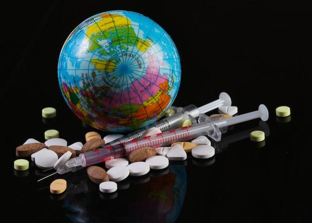 주사기와 글로브, 검은 색 표면에 환 약. 글로벌 예방 접종. 코로나 19 감염병 세계적 유행