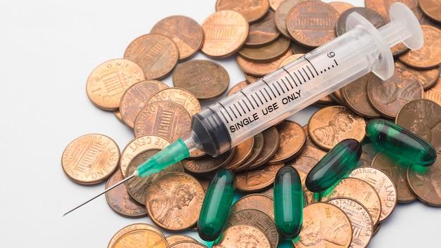 1 센트 동전 스택에 주사기와 녹색 캡슐 약물, 건강 관리 비용의 상징